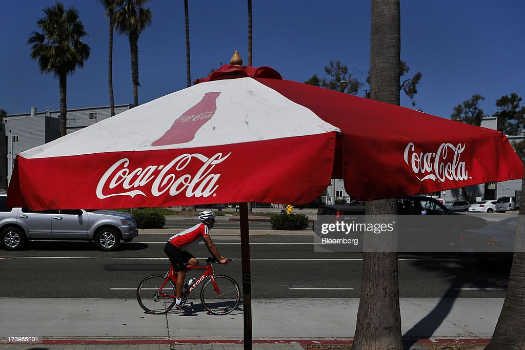A man bicycles past a Coca-Cola Co. branded umbrella outside a convenience store in Redondo Beach, California, U.S., on Monday, July 15, 2013. The Coca-Cola Co. is scheduled to release earnings data on July 16. Photographer: Patrick Fallon/Bloomberg via Getty Images