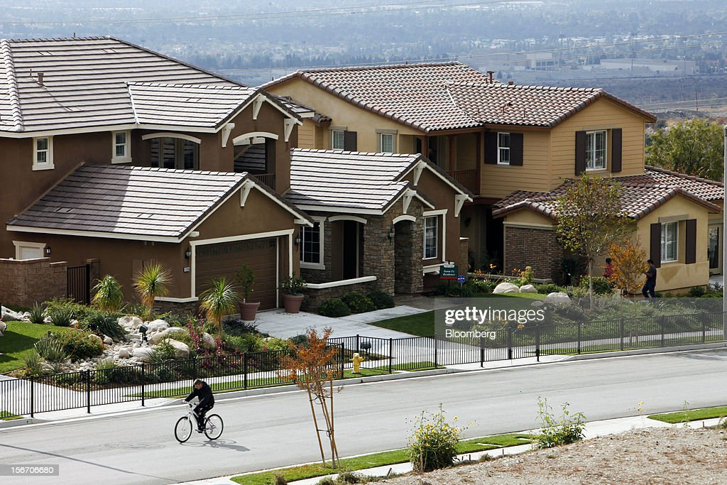 A man bicycles past model homes at the K. Hovnanian Homes Pasadera development in Rancho Cucamonga, California, U.S., on Sunday, Nov. 18, 2012. The U.S. Census Bureau is scheduled to release housing starts figures on Nov. 20. Photographer: Patrick T. Fallon/Bloomberg via Getty Images