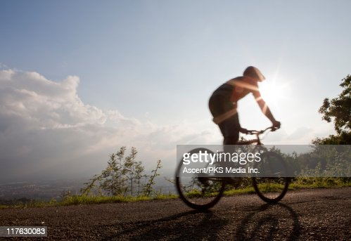 Man bikes along country road above city and hills : Stock Photo