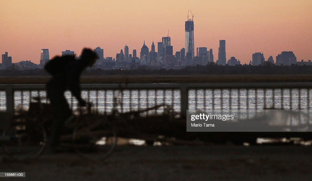 A man bikes past debris in the Rockaway neighborhood with the Manhattan skyline in the distance on November 6, 2012 in the Queens borough of New York City. The Rockaway section of Queens was one of the hardest hit areas. Many voters in New York and New Jersey are voting at alternate locations in the presidential election due to disruption from Superstorm Sandy as a Nor'easter storm approaches.