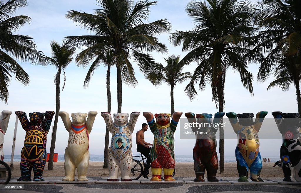 A man bikes past some of the 145 bear sculptures that form the 'United Buddy Bears' exhibition along famed Copacabana beach on May 6, 2014 in Rio de Janeiro. The project promotes tolerance in the world with the two-meter tall sculptures painted by artists from United Nations member states. The show officially opened today and will run through the 2014 FIFA World Cup which begins June 12.