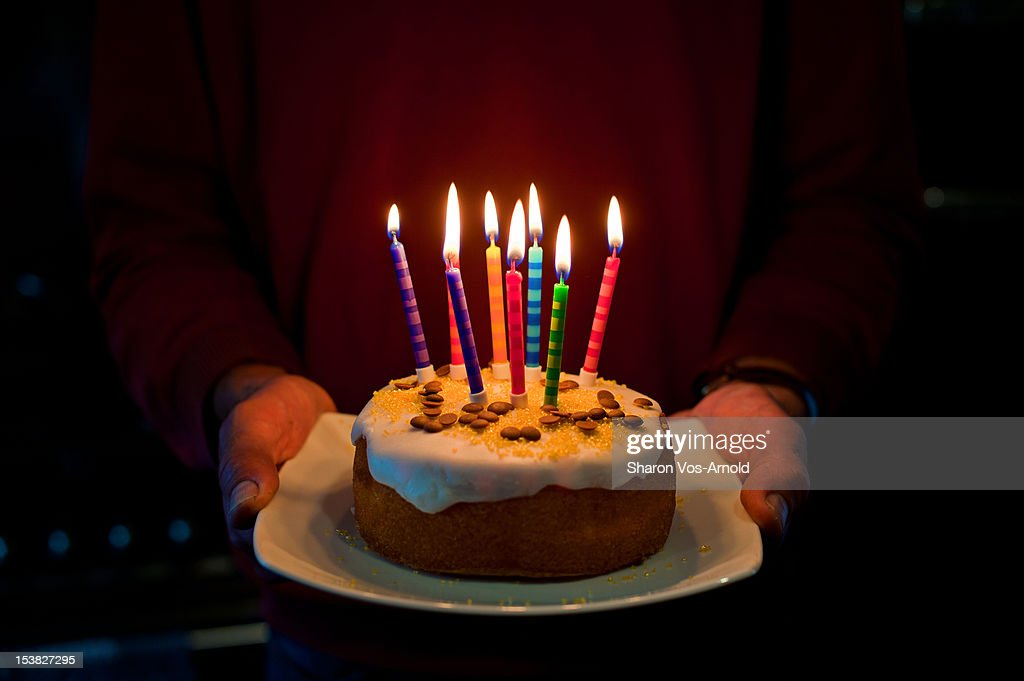 Man, birthday cake, 8 glowing coloured candles