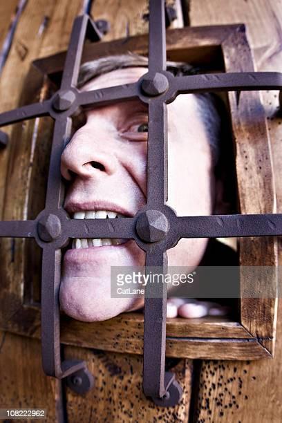 Mann beißen Bars des Gefängnisses