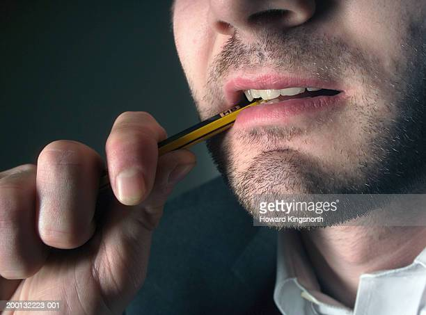 Man biting end of pencil, close-up