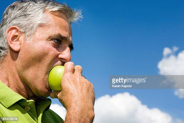 Man biting into apple