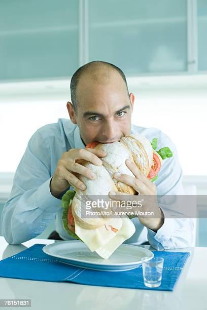 Man biting into large sandwich