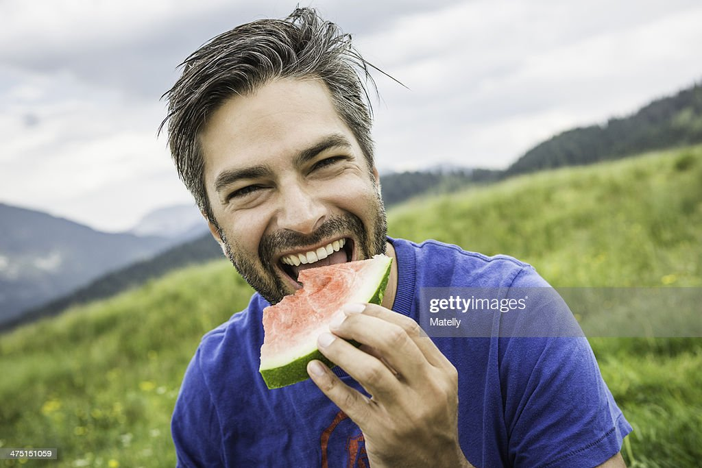 Man biting into watermelon