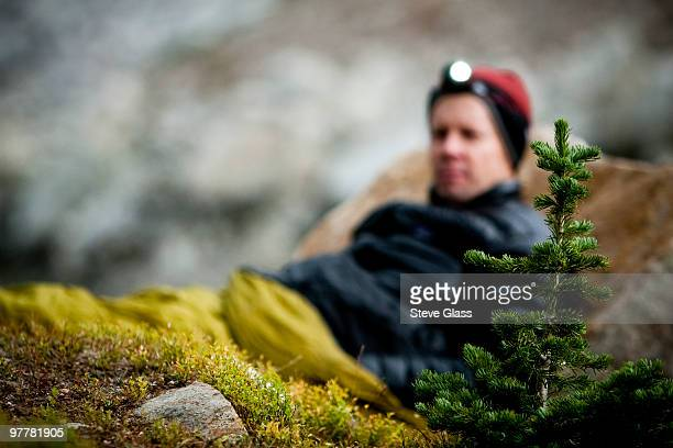 Man bivouacs in alpine meadow with the Snowy Range Mountains in the background.