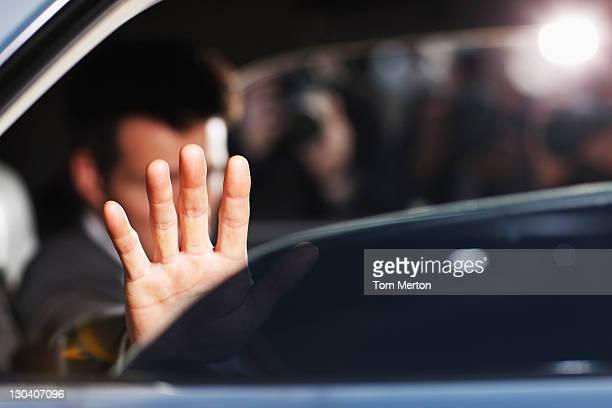 Man blocking photo in backseat of car