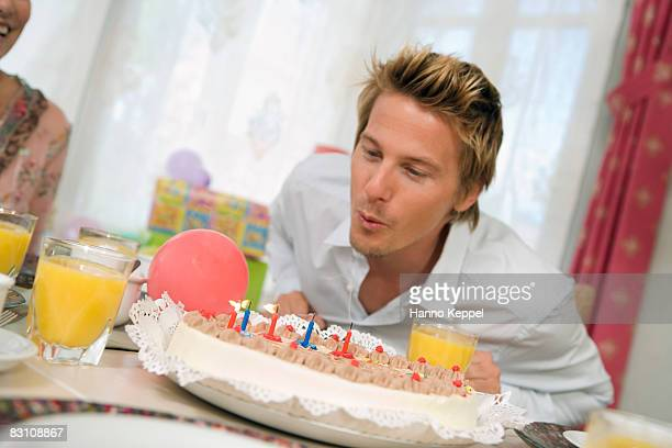 Man blowing candles on torte