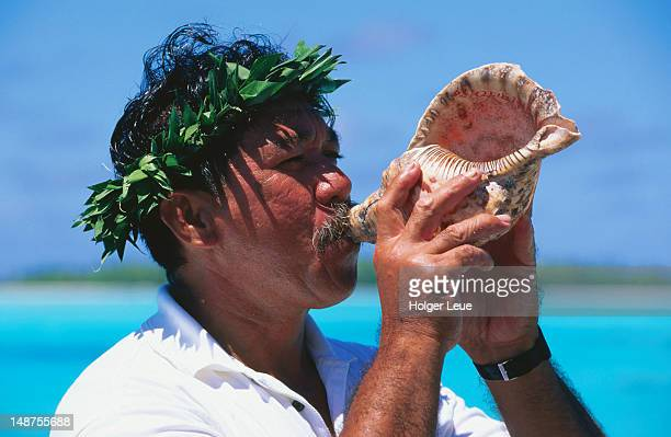 Man blowing conch shell.