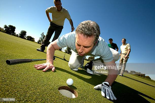Man blowing golf ball into hole