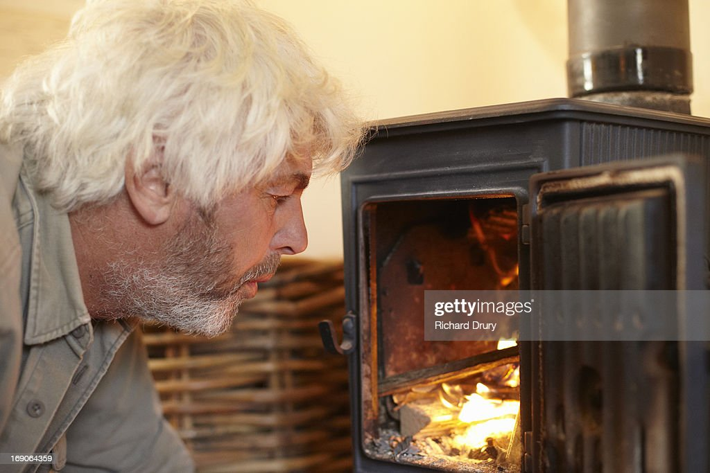 Man blowing on fire in woodburner