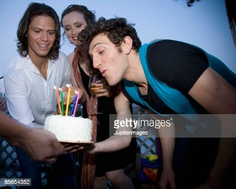Man blowing out candles on cake at birthday party : Stock Photo