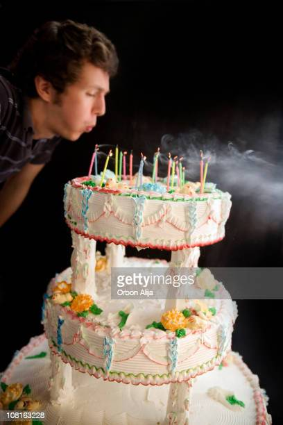 Man Blowing Out Candles on Tiered Cake