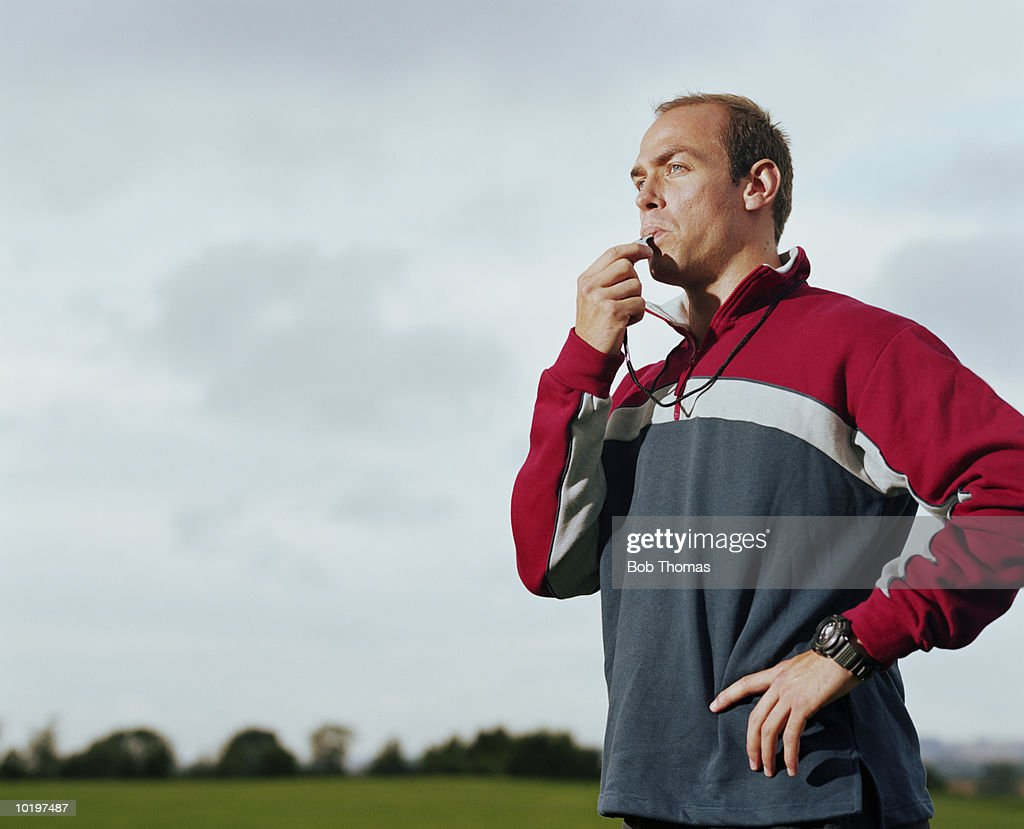 Man blowing sports whistle
