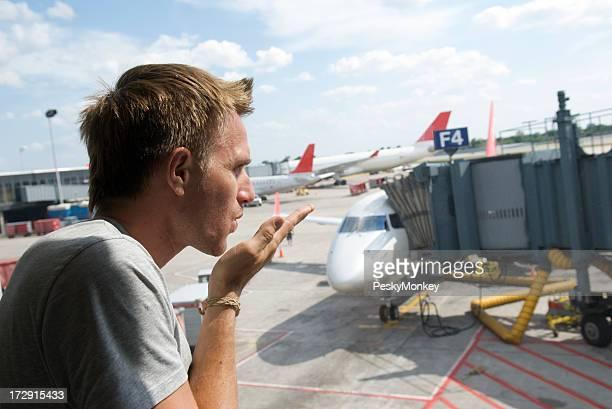Man Blows Kiss at the Airport Window