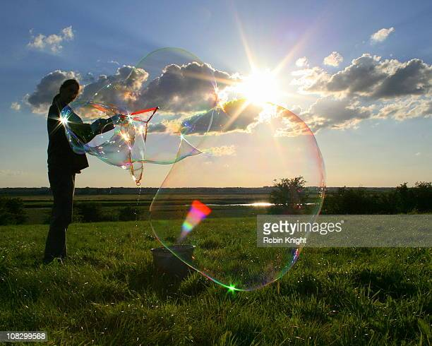 .A man blows large bubbles on a Summers Day