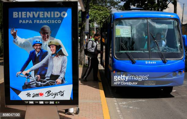 A man boards a bus at a bus stop where a sign welcoming Pope Francis is displayed ahead of his upcoming visit in Bogota on August 23 2017 Pope...