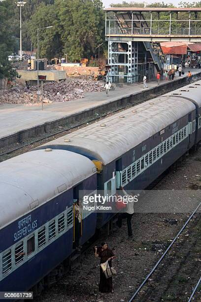 A man boards a sleeper class carriage of Indian Railways train at Raikabagh Palace Junction Jodhpur India