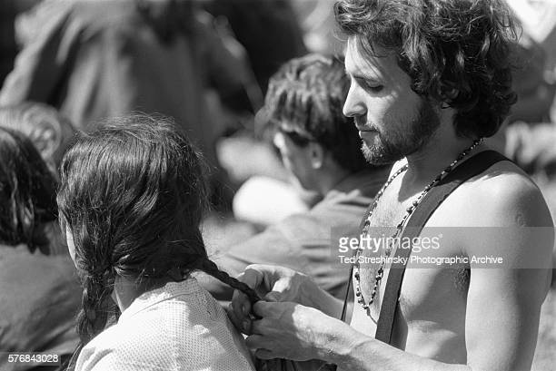 A man braids a woman's hair at a summer solstice celebration at Golden Gate Park in San Francisco