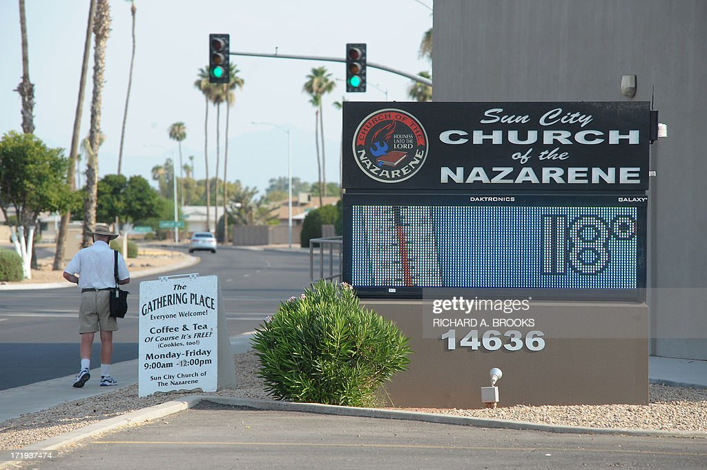 A man braves the afternoon heat as he walks past a local church in Sun City, Arizona showing temperatures of 118 F (48C) on June 29, 2013. Weather in the Phoenix area hit 119F, only three degrees off their all time high of 122F set just over 20 years ago, as a summer heat wave covered much of the west and southwest US. AFP PHOTO / RICHARD A. BROOKS