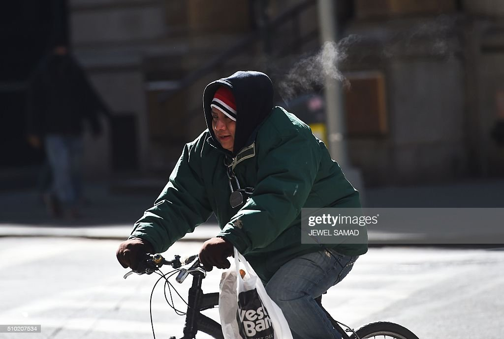 A man braves the cold weather as he rides his bike in downtown Manhattan, New York, on February 14, 2016. / AFP / Jewel Samad