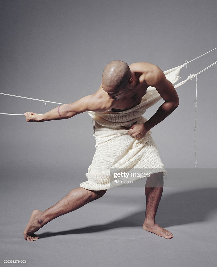 Man breaking free from fabric : Stock Photo
