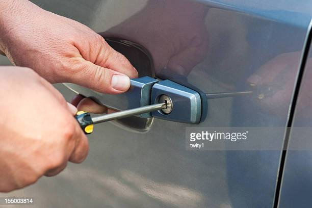 Man breaking into a blue car with a screwdriver