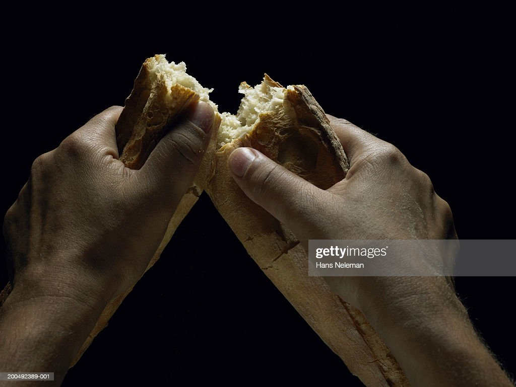 Man breaking piece of bread in half, close-up (personal perspective) : Stock Photo