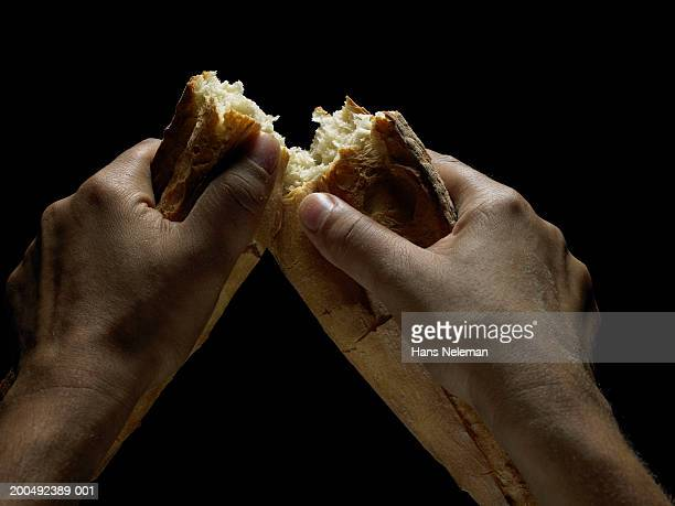 Man breaking piece of bread in half, close-up (personal perspective)