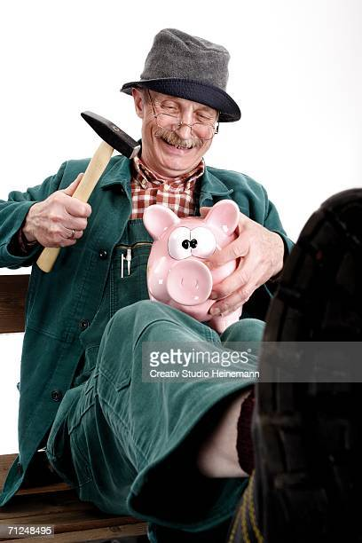 Man breaking piggy bank, close-up, smiling