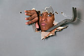 Man breaking through wall with crowbar