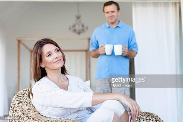 Man bringing girlfriend coffee on porch
