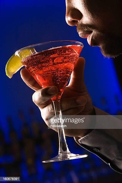 Man bringing martini up to lips in bar