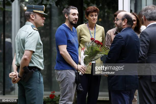 A man brings a bunch of flowers at the Embassy of Spain in Paris after a minute of silence on August 18 in tribute to victims and in solidarity with...