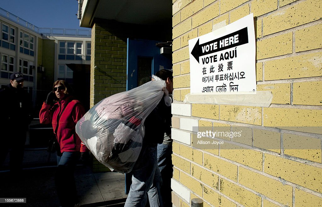 A man brings donated goods into a polling center doubling as a donation site November 6, 2012 in the Staten Island borough of New York City. As Staten Island continues to recover from Superstorm Sandy, a few polling stations have been relocated due to power outages or ongoing use as an evacuation center.