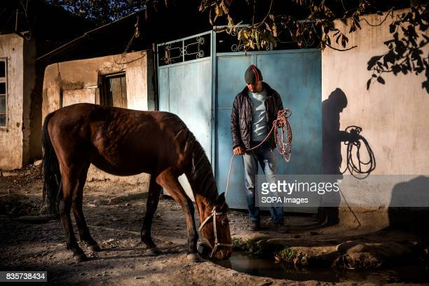 A man brings his horse to drink at an irrigation canal in the village of Beshkent Kyrgyzstan near where water is gathered for human consumption...