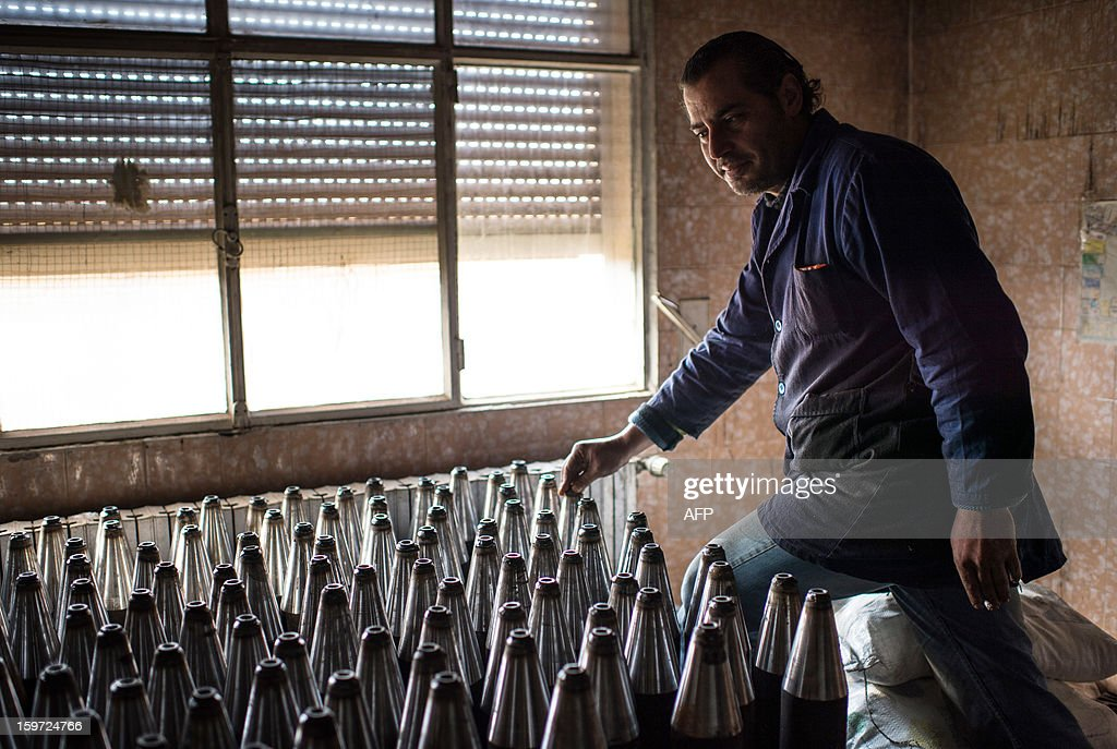 A man brings together hand made missiles in a secret factory on January 19, 2013 in Al-Bab, 30 kilometers from the northeastern Syrian city of Aleppo. Recycled or non explosed bombs recolted after shellings are used for the manufacturing and sugar as well for the propulsion. Each day, nearly 50 missiles are assembled for the Abu baker Brigade.