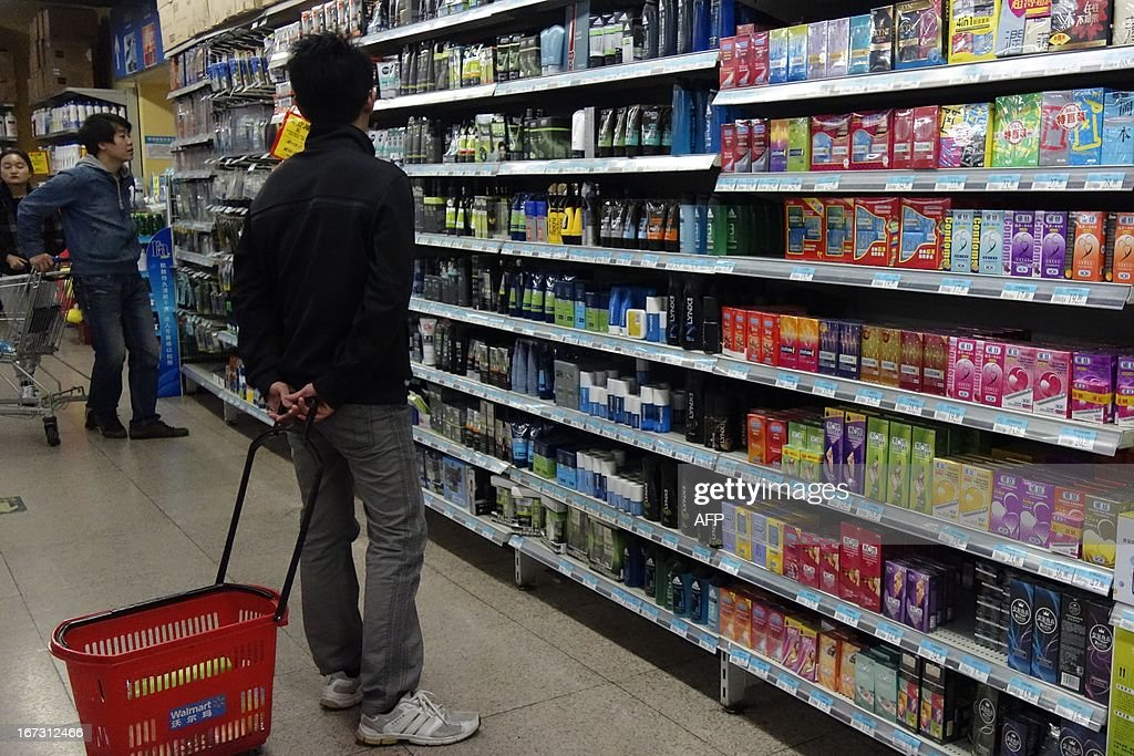 A man browses items for sale beside a shelf of condoms (R) at a supermarket in Beijing on April 24, 2013. Ghana is recalling a shipment of 120 million Chinese-made condoms distributed to charities in the country after testing showed that they were riddled with holes and prone to breaking, an official said on April 23. AFP PHOTO / WANG ZHAO