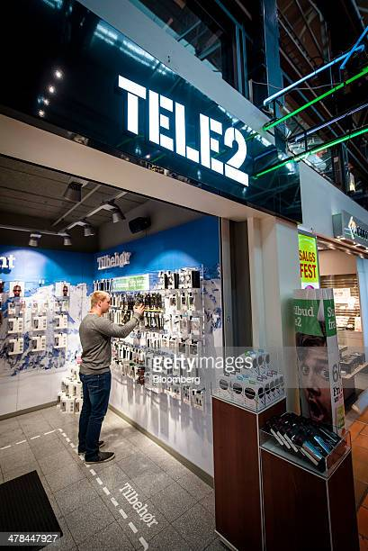 A man browses items inside a Tele2 AB mobile phone store at a shopping mall in Oslo Norway on Thursday March 13 2014 Tele2 AB the company controlled...