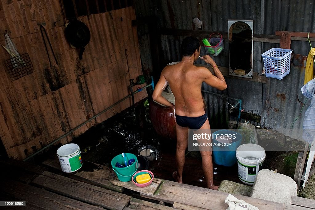 A man brushes his teeth in his bathroom outside his home at a slum in Bangkok on August 29, 2012. Thailand's economy has logged a second straight quarter of solid growth, buoyed by investment to repair factories damaged by last year's devastating floods and strong domestic demand, data showed. AFP PHOTO/ Nicolas ASFOURI