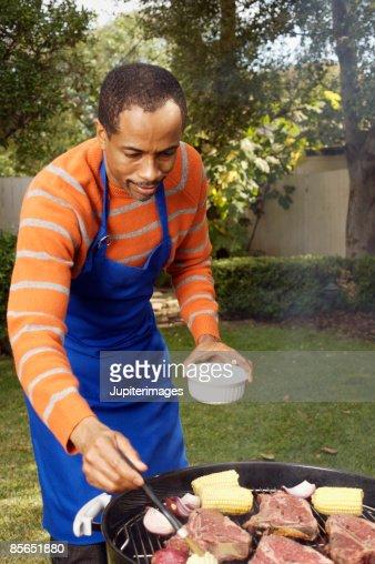 Man brushing corn with marinade