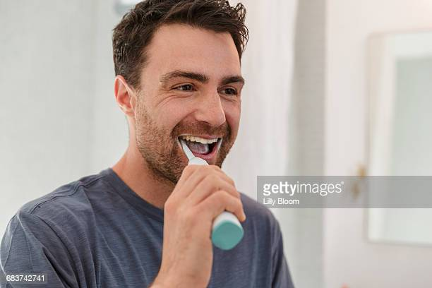 Man brushing teeth smiling