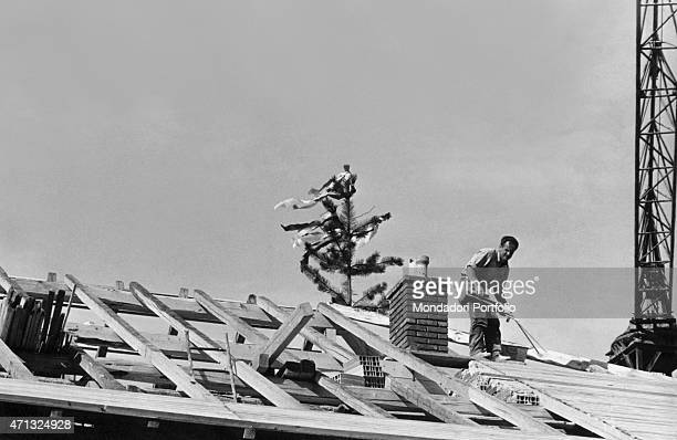 A man building a house roof decorated by a spruce with red and white ribbons as the Austrian flag German irredentists stroke terror into the village...