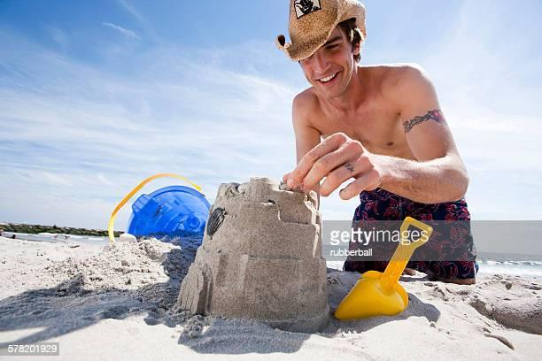 Man building a sand castle at the beach