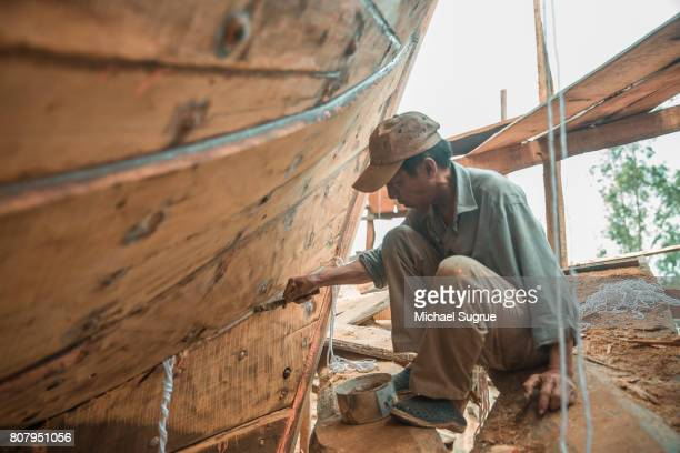 A man builds a large wooden boat on the bank of the Mekong River, Vietnam.