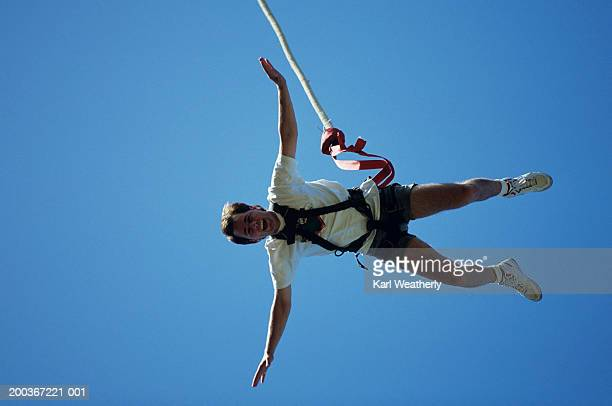 Man bungee jumping, seen against blue sky, view from below