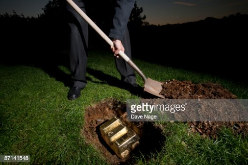 Man buring gold bars  in the ground
