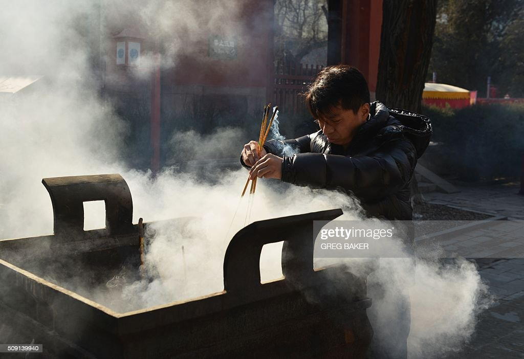 A man burns incense at a temple in Beijing during Lunar New Year celebrations in Beijing on February 9, 2016. Millions of Chinese are celebrating Spring Festival, the most important holiday on the Chinese calendar, which this year marks the beginning of the Year of the Monkey. AFP PHOTO / GREG BAKER / AFP / GREG BAKER